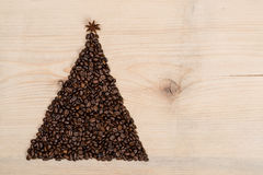 Christmas tree made from coffee beans on wooden background. Top view, copy space.Winter holidays concept. Stock Photography
