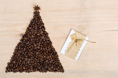 Christmas tree made from coffee beans on wooden background. Top Stock Photo