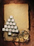 Christmas tree made of computer keys and glasses, Old paper background Royalty Free Stock Images