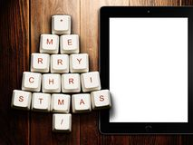 Christmas tree made of computer keys and tablet computer on wooden background Stock Photo