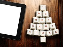 Christmas tree made of computer keys and tablet computer on wooden background Stock Photos
