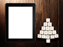 Christmas tree made of computer keys and tablet computer on wooden background Royalty Free Stock Images
