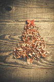 Simple Christmas tree arranged from sawdust, wood-chips on wooden background. Orange cute ribbon. stock photography