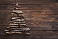 Christmas tree made of dry wooden branches with pine cones decor. Ation on wooden table background. View from above. New Year and Christmas card background Stock Image