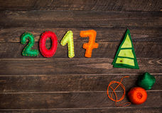 2017 Christmas tree made of felt. Childish New year background with christmas toy from felt on dark rustic wooden background. Royalty Free Stock Photography