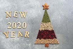 Christmas tree made of food on gray background. New year 2020. Creative idea, concept of vegetarian and vegan food. Top view, flat