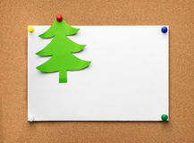 Christmas tree made of green paper and blank sheet on the cork b Stock Photos
