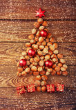 Christmas tree made of hazelnuts with red baubles and gifts Royalty Free Stock Photos