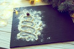 Christmas tree made out of a cooking flour on a dark background on a white wooden table Royalty Free Stock Image