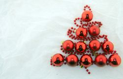 Christmas decorations, white and red. Christmas tree made of red pearls and shiny red balls on a white background Stock Photography