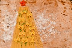 Christmas tree. Made from  row  fresh  spaghetti  and farfalle pasta and snow from parmesan cheese Royalty Free Stock Images
