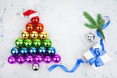 Christmas tree made of shiny decorations balls LGBT community rainbow flag colors, Santa Claus hat, gift box, blue ribbon, pine