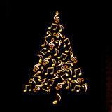 Christmas tree made of shiny golden musical notes on black Stock Photo