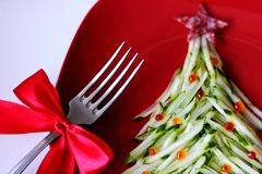 Christmas tree is made of sliced cucumber and decorated with red caviar. New year`s design of dishes. New year`s food stock images