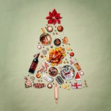 Christmas tree made with various Christmas food: turkey on platter, roasted ham, sweets and candies, cookies , mulled wine, ginger. Bread man decorated with gift royalty free stock photography