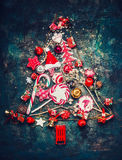 Christmas tree made with vintage holiday decoration and sweets on dark rustic background, top view Royalty Free Stock Photography