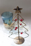 Christmas tree made of wire. A Christmas tree made of wire and a glass candle holder Royalty Free Stock Photo
