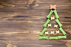 Christmas tree maden from canine chewing bones and cookies on wo. Oden background Royalty Free Stock Images