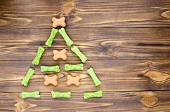 Christmas tree maden from canine chewing bones and cookies on wo. Oden background Royalty Free Stock Photos