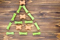 Christmas tree maden from canine chewing bones and cookies on wo. Oden background Stock Image