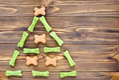 Christmas tree maden from canine chewing bones and cookies on wo. Oden background Royalty Free Stock Image