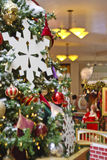 Christmas Tree in Mall with Santa. A beautiful custom decorated Christmas Tree with many ornaments and Santa Clause in background with child in lap OOF Stock Photos