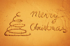 Christmas tree and Merry Christmas words drawn into sand Royalty Free Stock Images