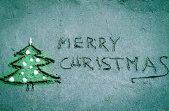 Christmas tree and Merry Christmas words drawn into sand Royalty Free Stock Photography