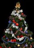Christmas tree with money dollar garland. Black background Royalty Free Stock Image