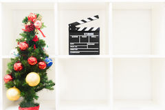 Christmas tree and movie clapper on empty white bookshelf Stock Image