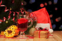 Christmas tree, mulled wine, oranges, red cap on abstract dark. Royalty Free Stock Images