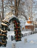 Christmas tree with multi-colored decorations outdoors and covered with snow in Tolgsky monastery. In Yaroslavl, behind the belfry of the monastery Royalty Free Stock Image