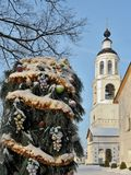 Christmas tree with multi-colored decorations outdoors and covered with snow in Tolgsky monastery in Yaroslavl. Behind the belfry of the monastery Royalty Free Stock Images