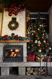 Christmas tree near burning fireplace decorated with christmas w Stock Photos