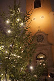 A Christmas tree near an old church. A Christmas tree with lights near an old church in Stockholm, Sweden, with a view of the branches of the tree and the faç stock image
