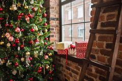 Christmas tree near the window, on the windowsill gift and balloons. wooden staircase stock photo