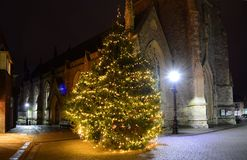 Christmas Tree at Newport, Isle of Wight. The Christmas tree and old Newport Minster Church look atmospheric and festive illuminated by fairy lights on the tree Stock Photo