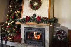 Christmas tree next to burning fireplace in a restaurant Royalty Free Stock Photo