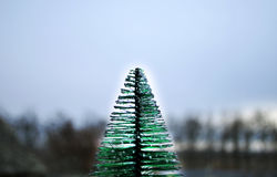 Christmas tree next to a cold window. Overlooking the trees with presets Royalty Free Stock Photography