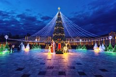 Christmas tree at night. Light from ornaments reflecting on tile. S. Cloudy sky on background. Wide shot royalty free stock images
