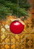 Christmas Tree Ornament. A red ornament hanging from a Christmas tree with a gold background Stock Photo