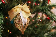 Christmas tree ornament. Closeup of decorative ornament hanging from Christmas tree with fairy lights in background stock image
