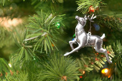 Christmas Tree Ornament Background. A selective focus still-life of a Reindeer Christmas ornament on a green Christmas tree background with copy space Stock Photography
