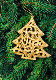 Christmas Tree ornament on Fir Tree Branches background. Christ. Golden  Christmas Tree ornament on Fir Tree Branches background. Christmas Card with festive Stock Image