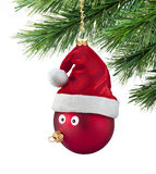 Christmas Tree Ornament Fun. A christmas ornament with a face and santa hat hanging from a christmas tree Stock Photo