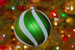 Christmas Tree Ornament. Large green and white and red christmas tree ornament with defocussed tree and lights behind it royalty free stock photography