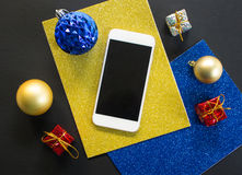 Christmas tree ornament and smartphone flat composition on black wooden table. Christmas tree ornament and smartphone flat composition. White smartphone with Stock Photography