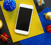 Christmas tree ornament and smartphone flat composition. White smartphone with black screen on table. Christmas or New Year mockup with personal gadget Royalty Free Stock Photography