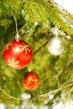 Christmas tree ornaments. A view of red and silver Christmas balls or baubles hanging from a Christmas tree bough royalty free stock photos