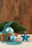 Christmas tree ornaments balls, beads and spruce branch in a bas. Ket on a background of cloth and boards Stock Photography